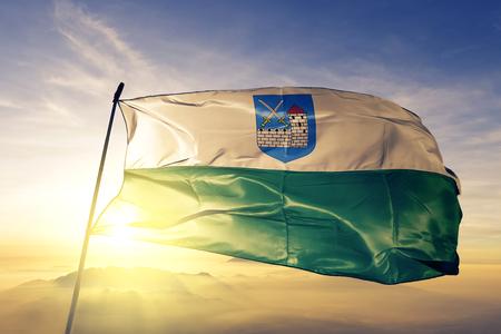 Ida-Viru county of Estonia flag textile cloth fabric waving on the top sunrise mist fog