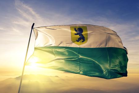 Parnu county of Estonia flag textile cloth fabric waving on the top sunrise mist fog