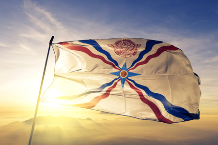 Assyrian people flag textile cloth fabric waving on the top sunrise mist fog 版權商用圖片