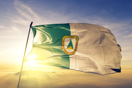 Cuiaba city of Brazil flag textile cloth fabric waving on the top sunrise mist fog