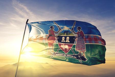 Kajiado county of Kenya flag textile cloth fabric waving on the top sunrise mist fog
