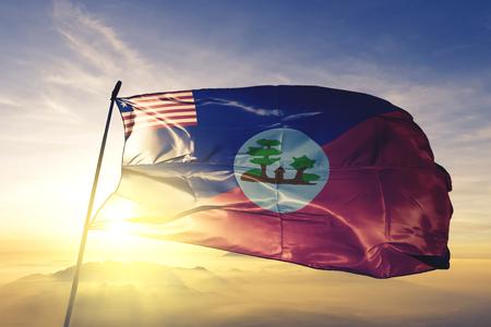 Comté de Montserrado du Libéria drapeau tissu textile ondulant sur le haut du brouillard du brouillard du lever du soleil Banque d'images