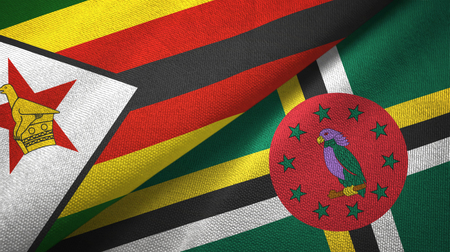 Zimbabwe and Dominica two folded flags together Reklamní fotografie