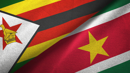 Zimbabwe and Suriname two folded flags together