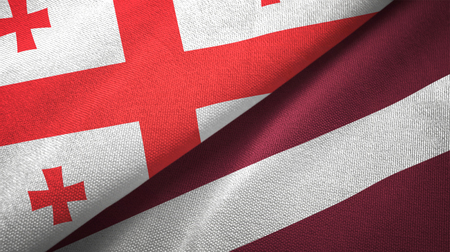 Georgia and Latvia flags together textile cloth, fabric texture Stock Photo