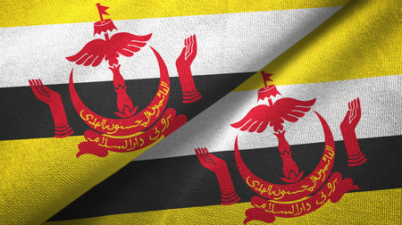 Brunei Darussalam flags together textile cloth, fabric texture. Text on brunei flag means - Always in service with God's guidance