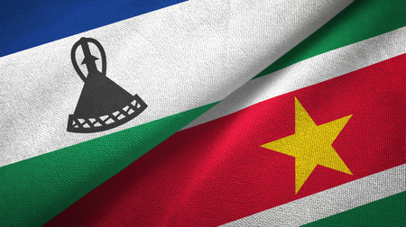 Lesotho and Suriname two flags textile cloth, fabric texture Stock Photo