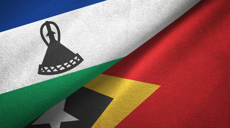 Lesotho and Timor-Leste East Timor two flags textile cloth, fabric texture Stock Photo