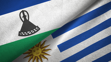 Lesotho and Uruguay two flags textile cloth, fabric texture Stock Photo