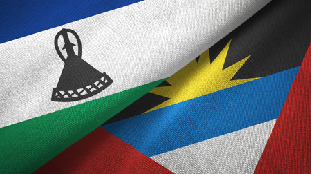 Lesotho and Antigua and Barbuda two flags textile cloth, fabric texture Stock Photo