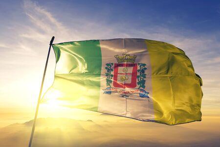 Ferraz de Vasconcelos of Brazil flag textile cloth fabric waving on the top sunrise mist fog