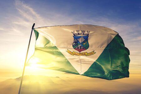 Cariacica of Brazil flag textile cloth fabric waving on the top sunrise mist fog