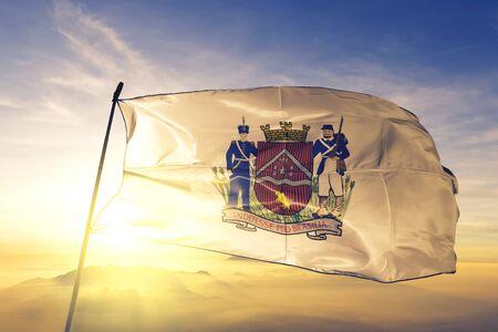 Uberaba of Brazil flag textile cloth fabric waving on the top sunrise mist fog