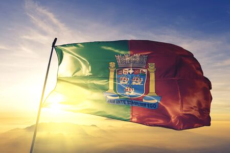Porto Seguro of Brazil flag textile cloth fabric waving on the top sunrise mist fog Фото со стока