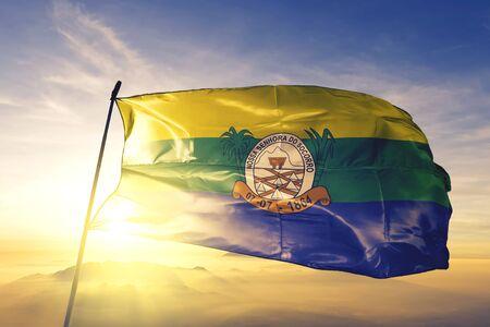 Nossa Senhora do Socorro of Brazil flag textile cloth fabric waving on the top sunrise mist fog Фото со стока