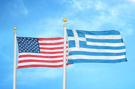 United States and Greece two flags on flagpoles and blue cloudy sky background