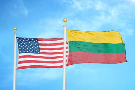 United States and Lithuania two flags on flagpoles and blue cloudy sky background