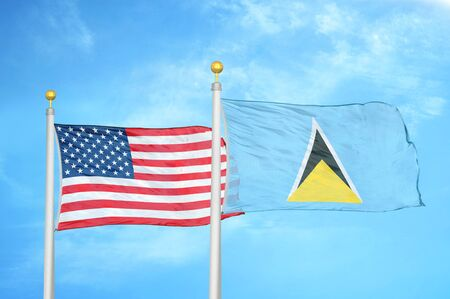 United States and Saint Lucia two flags on flagpoles and blue cloudy sky background