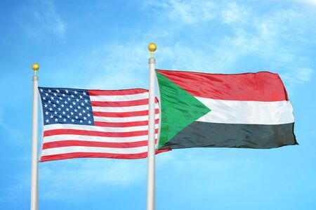 United States and Sudan two flags on flagpoles and blue cloudy sky background Stockfoto