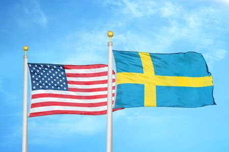 United States and Sweden two flags on flagpoles and blue cloudy sky background