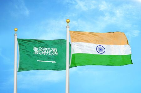 Saudi Arabia and India two flags on flagpoles and blue cloudy sky background