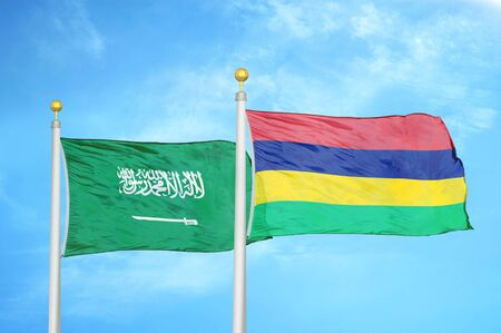 Saudi Arabia and Mauritius two flags on flagpoles and blue cloudy sky background