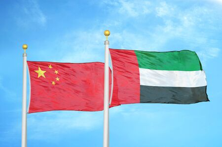 China and United Arab Emirates two flags on flagpoles and blue cloudy sky background