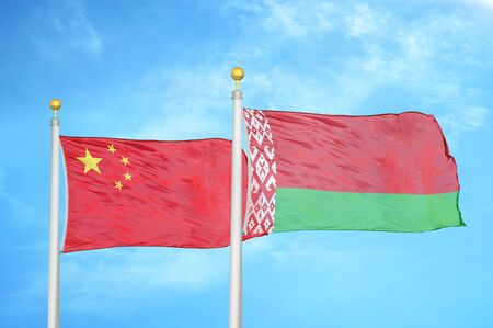 China and Belarus two flags on flagpoles and blue cloudy sky background