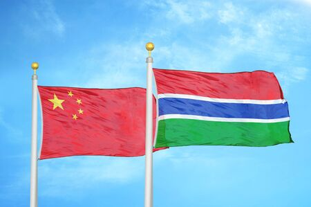 China and Gambia two flags on flagpoles and blue cloudy sky background