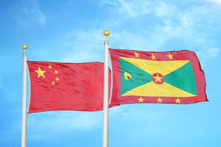 China and Grenada two flags on flagpoles and blue cloudy sky background 版權商用圖片