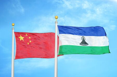 China and Lesotho two flags on flagpoles and blue cloudy sky background