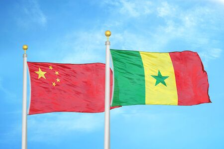 China and Senegal two flags on flagpoles and blue cloudy sky background 版權商用圖片
