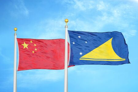 China and Tokelau two flags on flagpoles and blue cloudy sky background