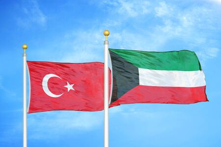 Turkey and Kuwait two flags on flagpoles and blue cloudy sky background Reklamní fotografie