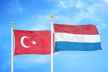 Turkey and Netherlands two flags on flagpoles and blue cloudy sky background