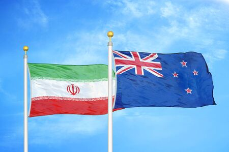 Iran and New Zealand two flags on flagpoles and blue cloudy sky background