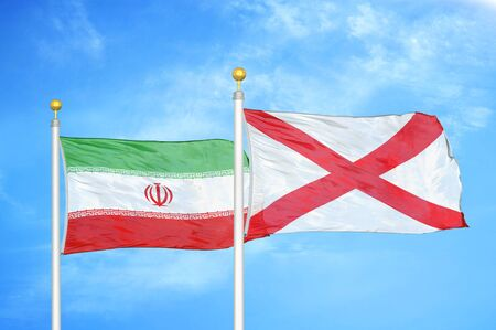 Iran and Northern Ireland two flags on flagpoles and blue cloudy sky background Stock Photo