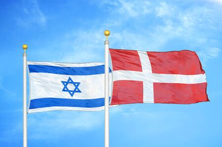 Israel and Denmark two flags on flagpoles and blue cloudy sky background