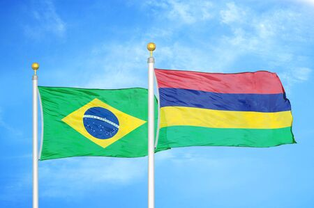 Brazil and Mauritius two flags on flagpoles and blue cloudy sky background
