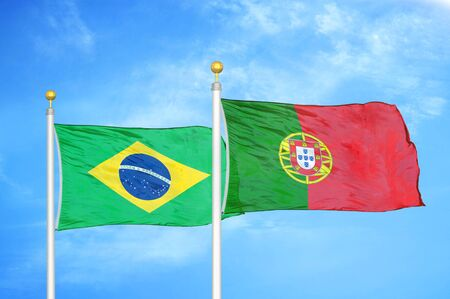 Brazil and Portugal two flags on flagpoles and blue cloudy sky background