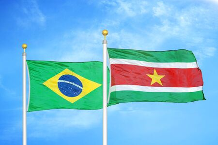 Brazil and Suriname two flags on flagpoles and blue cloudy sky background Stockfoto