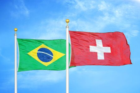 Brazil and Switzerland two flags on flagpoles and blue cloudy sky background