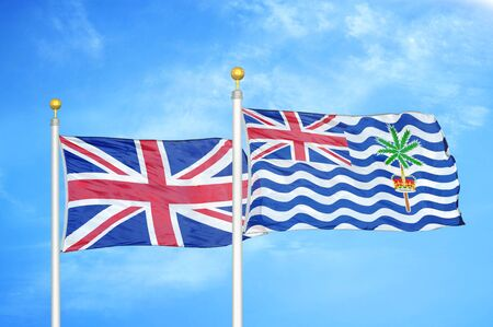 United Kingdom and British Indian Territory two flags on flagpoles and blue cloudy sky background