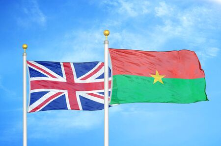 United Kingdom and Burkina Faso two flags on flagpoles and blue cloudy sky background