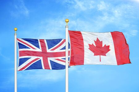 United Kingdom and Canada two flags on flagpoles and blue cloudy sky background