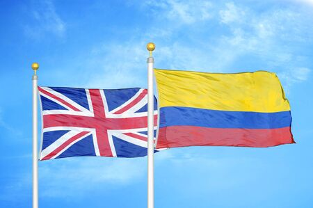 United Kingdom and Colombia two flags on flagpoles and blue cloudy sky background