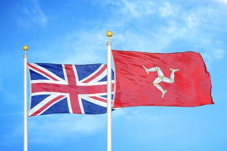 United Kingdom and Isle of Mann two flags on flagpoles and blue cloudy sky background Фото со стока