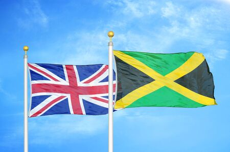 United Kingdom and Jamaica two flags on flagpoles and blue cloudy sky background Фото со стока