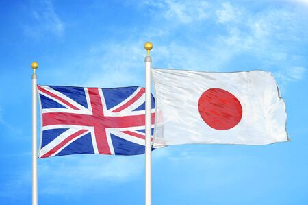 United Kingdom and Japan two flags on flagpoles and blue cloudy sky background Фото со стока