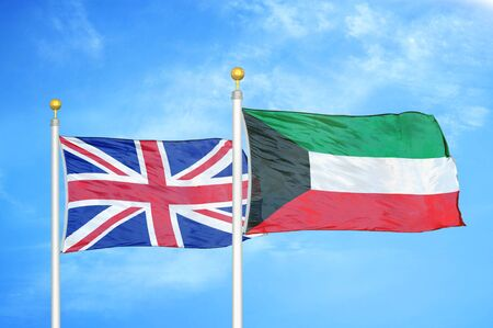 United Kingdom and Kuwait two flags on flagpoles and blue cloudy sky background Reklamní fotografie